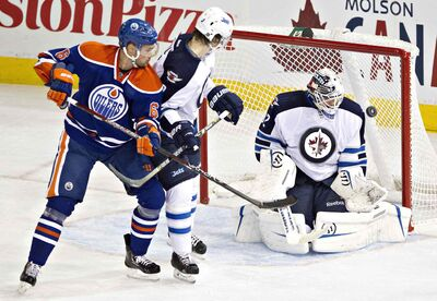 Goalie Edward Pasquale makes the save as Jacob Trouba and Oilers Jesse Joensuu battle in front during the second period in Edmonton on Monday.