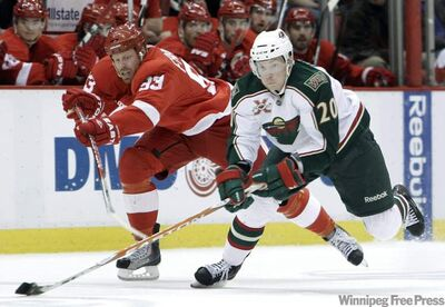 Detroit Red Wings left wing Johan Franzen (93), reaches for the puck in a game last April as Minnesota Wild right wing Antti Miettinen (20), controls it. The Winnipeg Jets have claimed Miettinen off waivers, though he will not play with them against his former team the Wild tonight.