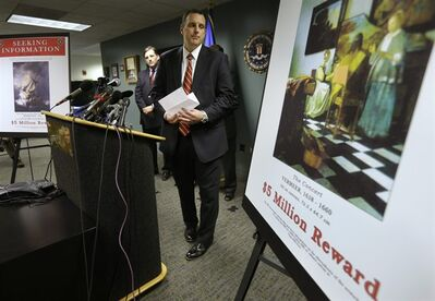 Federal Bureau of Investigation (FBI) Special Agent Geoff Kelly, center, looks in the direction of a poster that shows a Vermeer painting and lists a reward, right, after taking questions from reporters during a news conference at FBI headquarters in Boston, Monday, March 18, 2013. The FBI believes it knows the identities of the thieves who stole art valued at up to $500 million from Boston's Isabella Stewart Gardner Museum more than two decades ago. (AP Photo/Steven Senne)