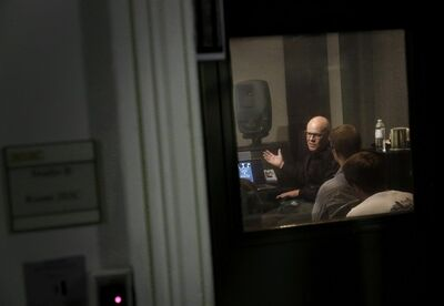 "In this Aug. 29, 2014 picture, musician Thomas Dolby is seen through a recording studio window as he speaks with students in his class, ""Sound on Film,"" at Johns Hopkins University's Peabody Institute music conservatory in Baltimore. Dolby, perhaps best known for his 1980's song ""She Blinded Me With Science,"" has made several careers at the nexus of sound and electronics. His newest role began Friday as a professor of the arts at Hopkins, and he hopes to show students how new technology creates fresh opportunities for composers and filmmakers to collaborate. (AP Photo/Patrick Semansky)"
