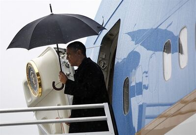 President Barack Obama uses an umbrella as he steps off Air Force One during his arrival at Albany International Airport, Tuesday, May 8, 2012, in Albany, N.Y. (AP Photo/Pablo Martinez Monsivais)