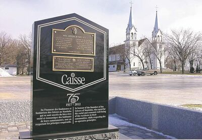 The monument erected last month to mark the 75th anniversary of the first credit union in Manitoba, established in St. Malo. The St. Malo Catholic Church is in the background.