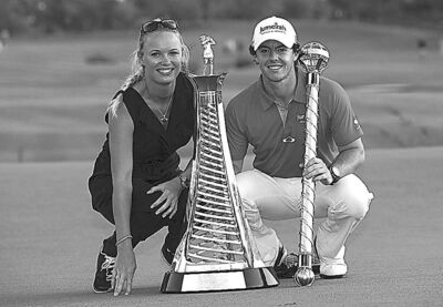 Rory McIlroy of Northern Ireland, right, holds the trophy with his girlfriend and Tennis player Caroline Wozniacki of Denmark after he wins the final round of DP World Golf Championship in Dubai, United Arab Emirates, Sunday Nov. 25, 2012. (AP Photo/Stephen Hindley)