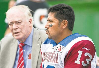 Montreal Alouettes medical staff member Dr. David S. Mulder talks to quarterback Anthony Calvillo after Calvillo took a hit during first half CFL action against the Saskatchewan Roughriders in Regina Saturday.