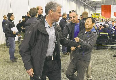 Chinese reporter Li Xue Jiang is hauled to the back of the room by RCMP on Friday.