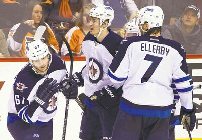 Michael Frolik (left) celebrates his goal with Mark Scheifele and Keaton Ellerby.