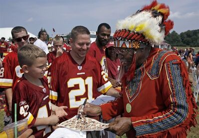 "FILE - In this Saturday, Aug. 4, 2012 file photo, Zena ""Chief Z"" Williams signs autographs during fan appreciation day at the Washington Redskins' NFL football training camp at Redskins Park in Ashburn, Va. President Barack Obama says that if he owned the Washington Redskins, he would ""think about changing"" the team name, wading into the controversy over a football nickname that many people deem offensive to Native Americans. Obama, in an interview on Friday, Oct. 4, 2013, said team names like the Redskins offend ""a sizable group of people."" He said that while fans get attached to the nicknames, nostalgia may not be a good enough reason to keep them in place. (AP Photo/Alex Brandon)"