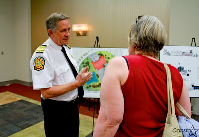 WFPS deputy chief Reid Douglas speaks to a resident at July 5 open house on the relocation of the Berry Street fire hall.