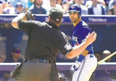Umpire Sam Holbrook runs Jose Bautista from the game after the slugger questioned his strike zone Sunday.
