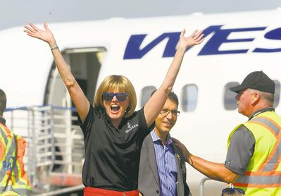 Brandon Mayor Shari Decter Hirst waves to those gathered Tuesday, followed by WestJet Encore president Ferio Pugliese.