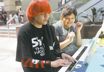Jason Beardy and his cousin, Monica Beardy, play the piano at Portage Place.