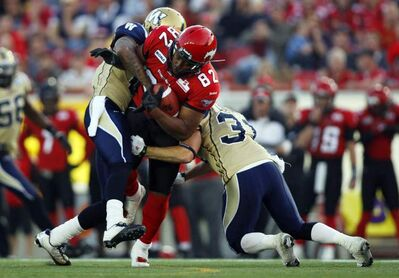 Winnipeg Blue Bombers' Johnny Sears, left, and Ian Logan, right, try to bring down Calgary Stampeders' Nik Lewis during first-quarter CFL  action in Calgary, Alta., Friday.