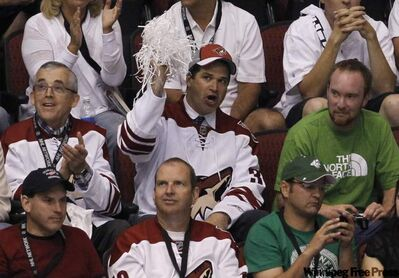 Chicago businessman Matthew Hulsizer, middle, who is trying to buy the Phoenix Coyotes, cheers on the team during the second period in Game 4 of a first-round NHL hockey Stanley Cup playoffs series against the Detroit Red Wings Wednesday in Glendale, Ariz.