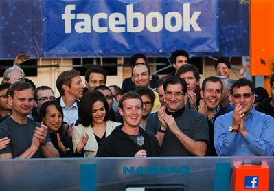 FOR USE AS DESIRED, YEAR END PHOTOS - FILE - FILE - In this May 18, 2012 file photo provided by Facebook, Facebook founder, Chairman and CEO Mark Zuckerberg, center, rings the Nasdaq opening bell from Facebook headquarters in Menlo Park, Calif. Robert Greifeld, second from right, CEO of the Nasdaq-OMX Stock Market, Inc. The social media company had its IPO. (AP Photo/Nasdaq via Facebook, Zef Nikolla, File)