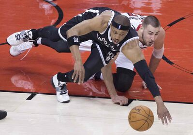 Brooklyn Nets' Paul Pierce, left, and Toronto Raptors' Jonas Valanciunas try to outmuscle one another in a battle for the ball.