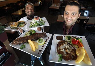 Cook Michael Jeffrey, left, with spanakopita and Greek salad; owner Essi Firooz holds Greek-style ribs and liver and onions.