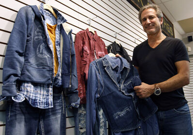 Michael Silver, CEO of Silver Jeans Co., with some Silver Jeans clothing. The company, best-known for wholesaling its clothes to  department stores and other retailers, is  preparing to open five stores in the U.S. in the next few months. Canadian stores are part of the two-to-three-year plan.
