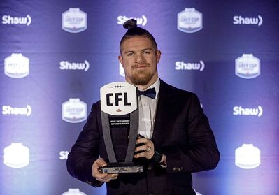 Winner of Most Outstanding Defensive Player, Winnipeg Blue Bombers' Adam Bighill, holds his award, during the Shaw CFL Awards in Edmonton on Thursday.