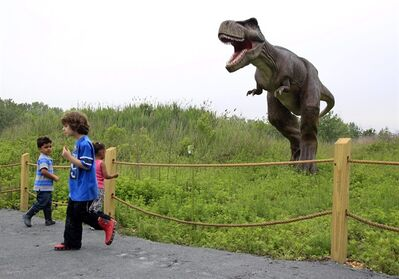 FILE - In this Friday, May 25, 2012 file photo, children stand near a life-size Tyrannosaurus Rex dinosaur model as it moves and growls in an interactive display at Field Station Dinosaurs in Secaucus, N.J. Scientists used to think T. rex stood tall, but they abandoned that idea decades ago. Now, the ferocious dinosaur is depicted in a bird-like posture, tail in the air and head pitched forward of its two massive legs. (AP Photo/Mel�Evans)