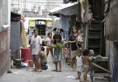 """In this June 20, 2013 photo, residents go about their daily chores at a poor neighborhood in Quezon city northeast of Manila, Philippines. As the Philippine economy skyrocketed 7.8 percent in the first quarter, outpacing China, the middle class in the Southeast Asian nation that has been held back by widespread poverty, political strife and corruption is for the first time in decades reaping the profits of an economic boom. Despite the stellar growth, joblessness soared 7.5 percent in April, up from 6.9 percent a year earlier. Another 19.2 percent were """"underemployed,"""" or part-time workers. (AP Photo/Bullit Marquez)"""