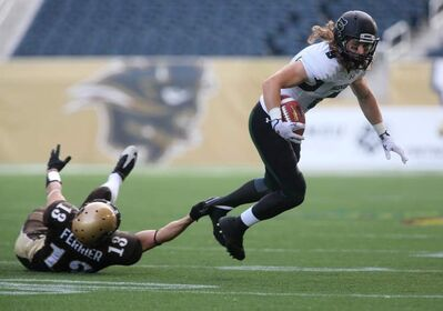 University of Manitoba Bisons' David Ferrier can't bring down University of Saskatchewan Huskies' Mitch Stevens at Investors Group Field, Saturday. Bisons lost a close one, 36-34.