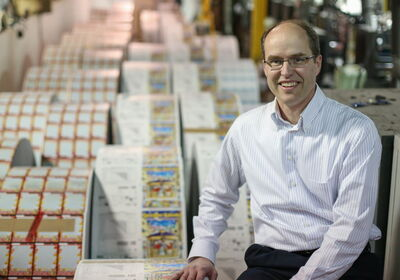 John Pollard, co-CEO of Pollard Banknote, poses with instant-win lottery tickets in the Winnipeg printing plant.
