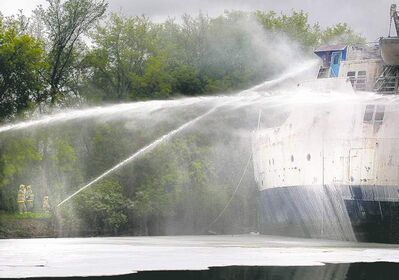 Firefighters stream water into the wheelhouse of the smoking hulk of the MS Lord Selkirk II Tuesday.