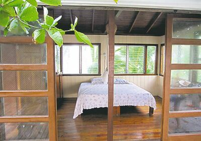 Sliding teak-wood doors open Sandy Cay's master bedroom to catch the Caribbean breeze in Sandy Cay, off Honduras.