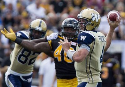 Winnipeg Blue Bombers' quarterback Buck Pierce makes a pass as teammate Terrence Edwards holds off Hamilton Tiger-Cats' Eric Norwood in Guelph, Ont., Saturday.
