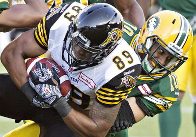 Donovan Alexander (right) tackles Hamilton Tiger-Cats' Onrea Jones: the ex-Eskimo had seven interceptions in 51 games.