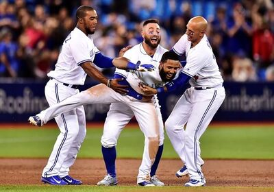 Toronto Blue Jays shortstop Richard Urena (7) is mobbed by teammates Teoscar Hernandez, left to right, Kevin Pillar and Ryan Goins after hitting a game winning RBI single against the Baltimore Orioles during ninth inning American league baseball action in Toronto on Tuesday, Sept. 12, 2017. THE CANADIAN PRESS/Frank Gunn