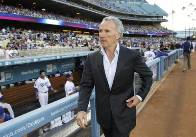 FILE - This June 8, 2010 file photo shows Frank McCourt walking by the dugout on the field before the Los Angeles Dodgers baseball game against the St. Louis Cardinals, in Los Angeles. The McCourt's have reached a divorce settlement that gives Frank McCourt control of the Dodgers and Jamie McCourt about $130 million, making it one of California's costliest divorces, according to a report published Monday, Oct. 17, 2011. (AP Photo/Danny Moloshok, File)
