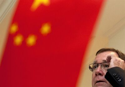 New Zealand Foreign Minister Murray McCully adjusts his glasses behind a Chinese national flags as he listens to a question from a journalist during a group interview in Beijing Thursday, Aug. 22, 2013. Murray has assured Chinese leaders of his country's commitment to food quality standards following safety scares over milk exports. (AP Photo/Andy Wong)