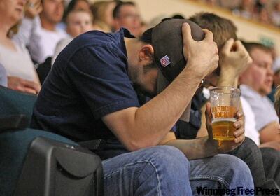 A Manitoba Moose fan reacts in disbelief after the Hershey Bears score their third goal in the first period.
