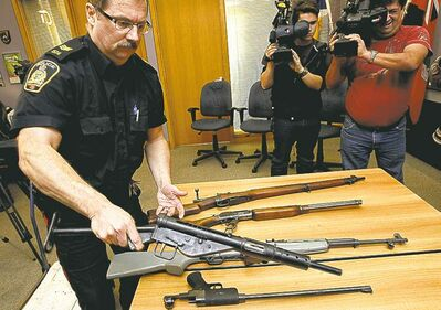Mike Deal / Winnipeg Free Press Patrol Sgt. Kevin Wiens sets out a few of the 1,700 firearms handed over to police.