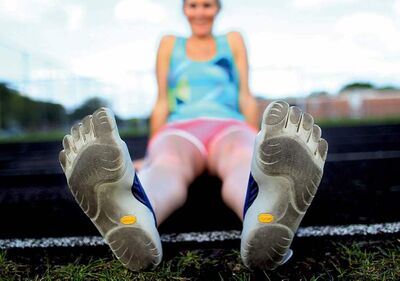 Vibram FiveFingers shoes have flat soles and individual toes that encourage runners to strike the ground with the front of their feet.