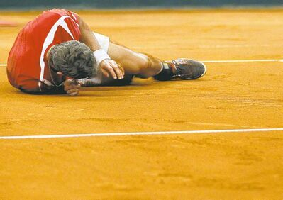 Canada's Vasek Pospisil collapses after losing his Davis Cup semifinal match against Janko Tipsarevic in Serbia on Sunday.