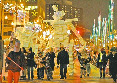 Art City's gigantic Styrofoam robots tower over parade participants during the 104th annual Santa Claus Parade in Winnipeg on Saturday.
