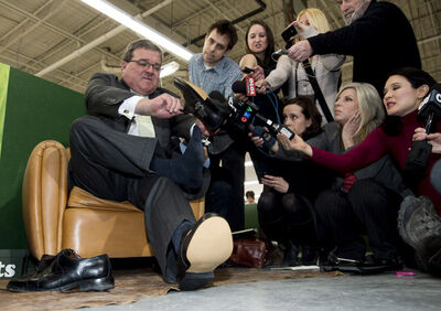 Finance Minister Jim Flaherty puts on his annual pre-budget shoes at the Roots Leather Factory in Toronto on Wednesday.