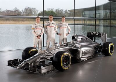 This photo provided Friday Jan. 24, 2014 by McLaren shows the new MP4-29 with drivers Kevin Magnussen of Denmark, left, Jenson Button of Britain, center, and Stoffel Vandoorne of Belgium at the McLaren Technology Centre in Woking, England. (AP Photo/McLaren)