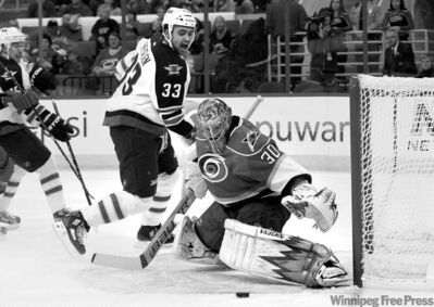 Gerry Broome / The Associated PressHurricanes goalie Cam Ward defends the goal as Jets defenceman Dustin Byfuglien makes one of his frequent forays into enemy territory.