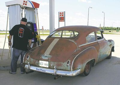 Willy pumps gas into his rusty but trusty 1949 Pontiac Silver Streak on route to the Devils Run.
