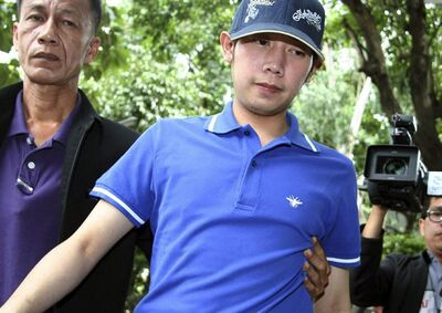 Vorayuth Yoovidhya, a grandson of late Red Bull founder Chaleo Yoovidhaya, is taken by a plain-clothes police officer for investigation Monday, Sept. 3, 2012 in Bangkok, Thailand. Vorayuth, believed to be in his late 20s, is suspected of driving a Ferrari that struck and killed a policeman and then dragged the officer's body down a Bangkok street in an early-morning, hit-and-run accident, police said Monday. (AP Photo) THAILAND OUT