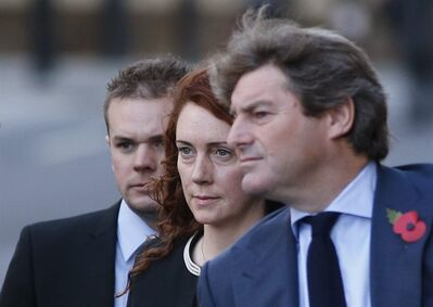 Former News of the World editor Rebekah Brooks, center, along with her husband Charlie, right, arrives at Central Criminal Court in London, Tuesday, Oct. 29, 2013. Once one of the most powerful people in the British media, Brooks, a senior executive for media mogul Rupert Murdoch and associate of Prime Minister David Cameron, is accused on charges of hacking phones and bribing officials while at the now-shuttered Murdoch tabloid. (AP Photo/Lefteris Pitarakis)