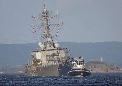 The damaged USS Fitzgerald is being towed by a tugboat in the waters near the U.S. Naval base in Yokosuka, southwest of Tokyo, after the U.S. destroyer collided with the Philippine-registered container ship ACX Crystal in the waters off the Izu Peninsula Saturday, June 17, 2017. Crew members from the destroyer USS Dewey were helping stabilize the damaged USS Fitzgerald after its collision off the coast of Japan before dawn Saturday, leaving seven sailors missing and at least three injured. (AP Photo/Eugene Hoshiko)