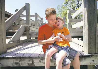 Griffin with his little brother Tyler on Windsor School's old play structure. The Class of 2017 threw two fundraisers Friday to replace it with something newer, and more accessible.
