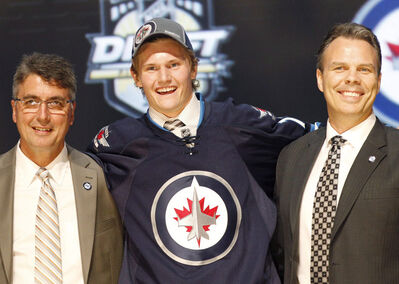 Jacob Trouba, center, a defenseman, stands with officials from the Winnipeg Jets after being chosen ninth overall in the 2012 NHL hockey draft in Pittsburgh.