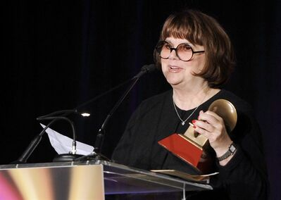 """FILE - In a Nov. 9, 2011, file photo Linda Ronstadt accepts the Life Time Achievement award at the Latin Recording Academy Lifetime Achievement Award and Trustees Award ceremony in Las Vegas. In an AARP Magazine article posted online Friday, Aug. 23, 2013, Ronstadt says that she was diagnosed with Parkinson's disease and """"can't sing a note."""" (AP Photo/Chris Pizzello, file)"""