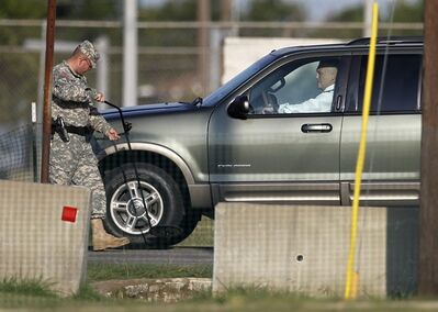 U.S. Army Col. Steve Henricks, a member of the prosecution, has his vehicle inspected upon arriving at the Lawrence H. Williams Judicial Center as proceedings in the court martial of U.S. Army Maj. Nidal Malik Hasan continue, Thursday, Aug. 22, 2013, in Fort Hood, Texas. (AP Photo/Tony Gutierrez)