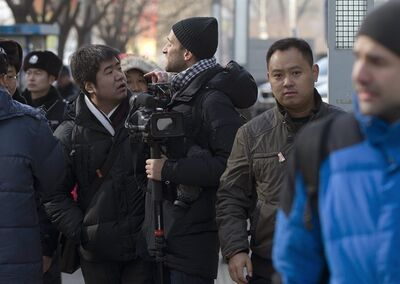 A foreign journalist argues with policemen while he and other media are urged to stay away from the No. 1 Intermediate People's Court, where legal scholar and founder of the New Citizens movement Xu Zhiyong attends his trial in Beijing Wednesday, Jan. 22, 2014. The trial of the prominent activist who has led a grassroots campaign demanding a fairer society and official accountability to better fight corruption started in Beijing, while police blocked journalists and supporters from getting near. Xu stood trial Wednesday, accused of disrupting public order. (AP Photo/Andy Wong)